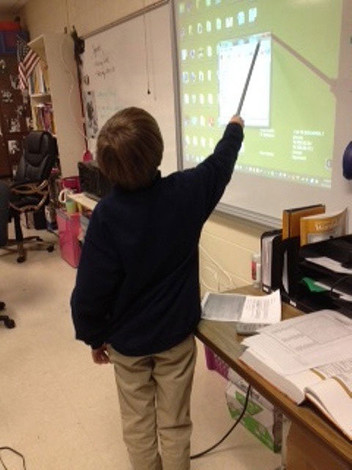 Student uses interactive whiteboard to share information with others.