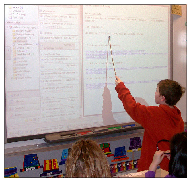 Students are utilizing electronic whiteboard at interactive classroom.